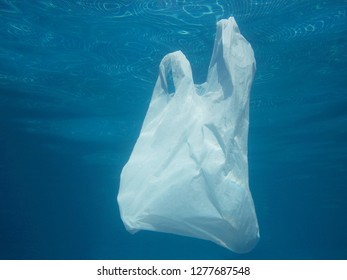 Plastic bag floating into the water. Polluted enviromental. Recycle garbage