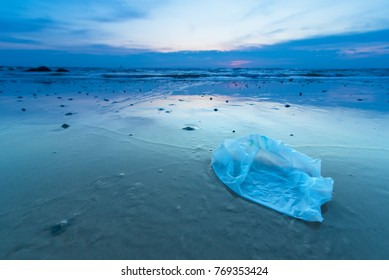 Plastic bag on the beach in the sunrise