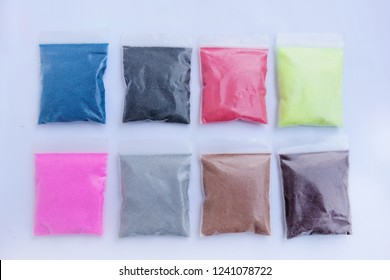 plastic bags with colored sand on white background
