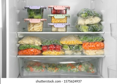 Plastic bags and containers with different frozen vegetables in refrigerator