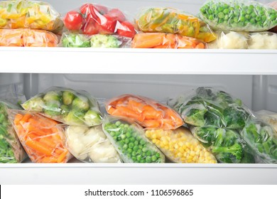 Plastic bags with deep frozen vegetables in refrigerator