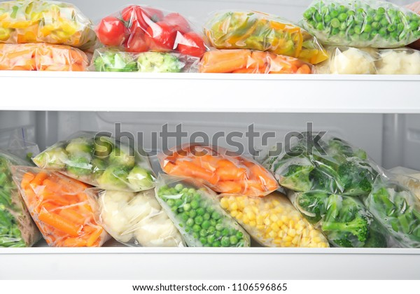 Plastic bags with deep frozen vegetables in refrigerator