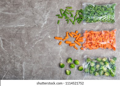 Plastic bags with different frozen vegetables on table, top view