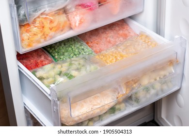 Plastic bags with different frozen vegetables in refrigerator. Food storage
