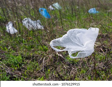 Plastic bags dumped in the meadow contaminate environment