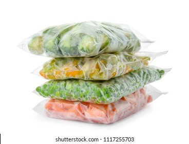 Plastic bags with frozen vegetables on white background