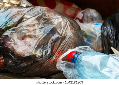plastic bags of garbage and a bottle in a container before disposal. waste recycling as an aid to nature