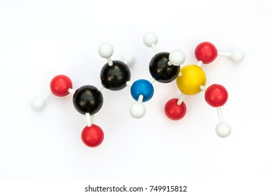 Plastic ball-and-stick model of glyphosate (chemical formula: C3H8NO5P) on a white background. Glyphosate is used world wide as a a systemic herbicide to kill weeds.