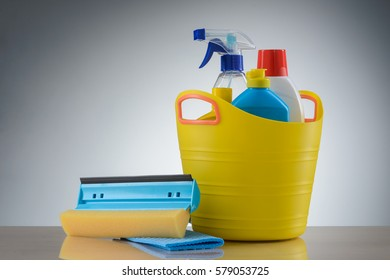 Plastic basin with a multi-purpose spray, a dishwashing liquid, a fabric conditioner, a bleach. Window cleaning brush and cellulose kitchen cloth, reflection on the table. Neutral background.