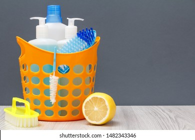 Plastic basket with bottles of dishwashing liquid, glass and tile cleaner, detergent for microwave ovens and stoves with brushes and lemon on gray background. Washing and cleaning concept.