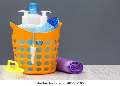 Plastic basket with bottles of dishwashing liquid, tile cleaner, detergent for microwave ovens and stoves. Brushes, garbage bags on gray background. Washing and cleaning kit.