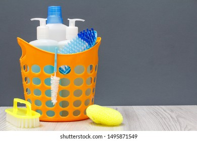 Plastic basket with bottles of dishwashing liquid, glass and tile cleaner, detergent for microwave ovens and stoves with brush and sponges on gray background. Washing and cleaning kit.