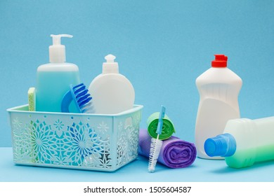 Plastic basket, bottles of dishwashing liquid, glass and tile cleaner, brushes, garbage bags on blue background. Washing and cleaning concept.