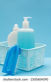 Plastic basket with bottles of dishwashing liquid, glass and tile cleaner, brush on blue background. Washing and cleaning concept.