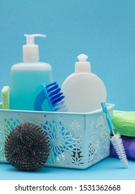 Plastic basket with bottles of dishwashing liquid, glass and tile cleaner, brushes on blue background. Washing and cleaning products.