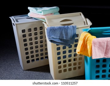 Plastic baskets with color towels on dark background