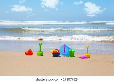 Plastic beach toys on beach with sea and clouds in background