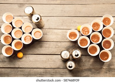 Plastic beer pong cups and cans on wooden table, top view