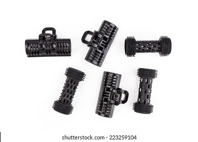Plastic black hair curlers on a white background