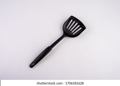 Plastic black spatula for a frying pan isolated on white background. New spatula. Spatula for cook food