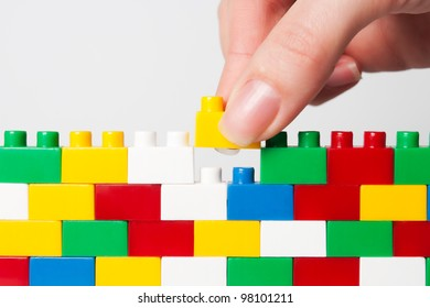 plastic block in hand building wall isolated on white.