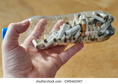 A plastic bottle containing cigarette butts in a man's hand, on wooden background