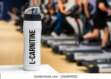 Plastic bottle or cup with L-Carnitine drink close up