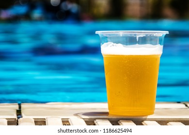 Plastic bottle with draft beer in sunny day in summer near swimming pool