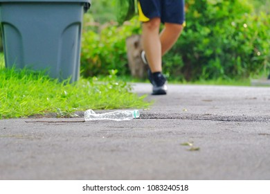 A plastic bottle of drinking water littering on the road ground floor at the green park with blur trash bins and a man running on the pathway for green environment concept