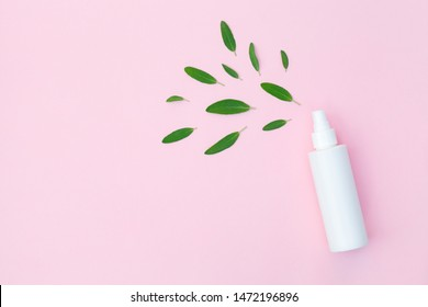 plastic bottle of facial moisturizing toner or hair spray and green herbal leaves isolated on pastel pink background, flay layout, top view, copy space, natural organic beauty product