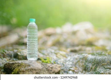 Plastic bottle with fresh drinking water on nature background.