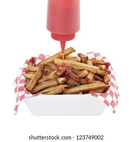 Plastic bottle of ketchup pouring in to a bowl of French fries
