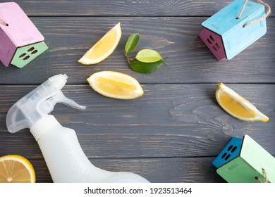 A plastic bottle with liquid for cleaning glass, plumbing, tiles or floors and green leaves and lemon slices on a wooden background with space for text. Natural organic cleaning agent. Eco-concept.