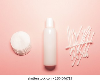 Plastic bottle with lotion, cotton swabs and cotton pads on a pink background