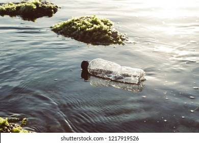 A plastic bottle in the ocean. Plastic pollution concept.  Single-use plastic is a human addiction that is destroying our planet and impacts our waters, sea life and humans.