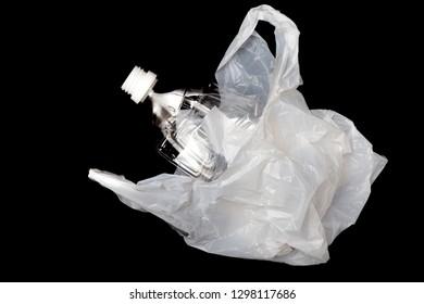 Plastic bottle with plastic shopping bag on black background