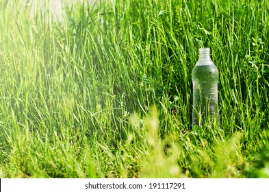 plastic bottle with water on a background of green grass