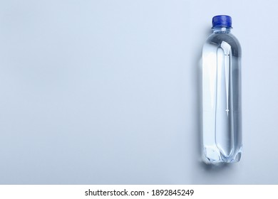 Plastic bottle with water on white background, top view. Space for text