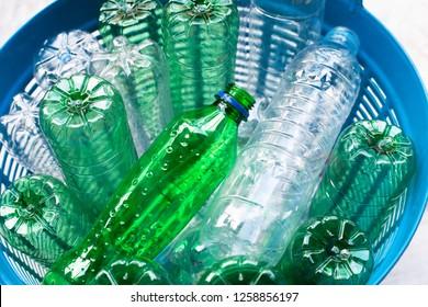 Plastic bottles in blue waste basket.