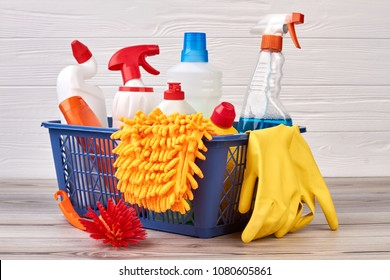 Plastic bottles with cleaning liquid in basket. Colorful detergent containers, yellow rubber gloves and cleaning brush in laundry basket.