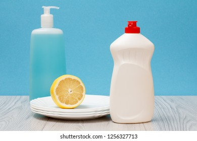 Plastic bottles of dishwashing liquid, glass and tile cleaner, clean plates and lemon on blue background. Washing and cleaning concept.
