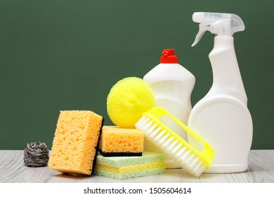 Plastic bottles of dishwashing liquid, glass and tile cleaner, yellow brush and sponges on laminate flooring and green background. Washing and cleaning concept.