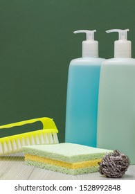 Plastic bottles of dishwashing liquid, glass and tile cleaner, brush, metal sponge with green background. Washing and cleaning products.