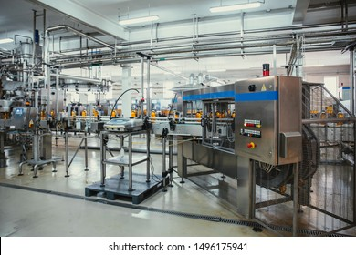 Plastic bottles with juice on automated conveyor line or belt in modern beverage plant or factory production, toned