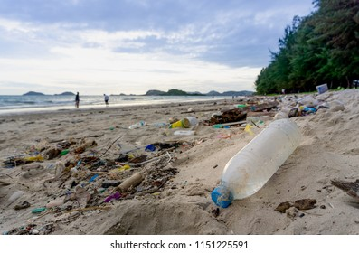 Plastic bottles left on the dirty sand beach with various garbages such as  fishing nets,foam food boxs, bamboo logs, coconut fruit, glass bottles etc.