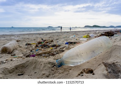 Plastic bottles left on the dirty sand beach with various garbage such as  fishing nets,foam food boxs, bamboo logs, coconut fruit, glass bottles etc.