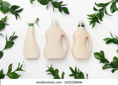 Plastic bottles with liquid detergent, antibacterial gel with natural plant extract and green leaves on white background. Eco style cleaning concept