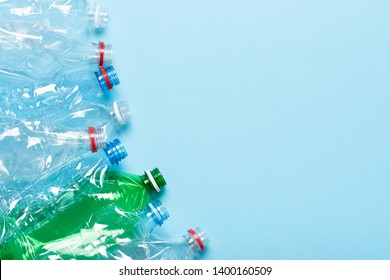 Plastic bottles on blue background top view. Recycle plastic waste pollution concept border with copy space.