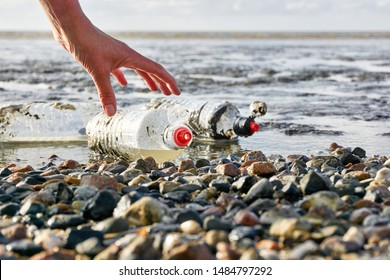 Plastic bottles on stony beach picked up by hand of a woman. Concept of cleaning plastic pollution of the sea and marine life. Beat Plastic Pollution. Blue sky with clouds and copy space.