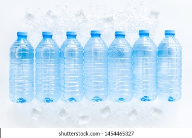 Plastic bottles with pure water and ice on white background top view